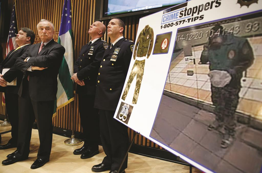 Police Commissioner Bill Bratton (2nd L) on Monday looks at a video frame of cop-killer Ismaaiyl Brinsley during a news conference at police headquarters.  (AP Photo/Seth Wenig)