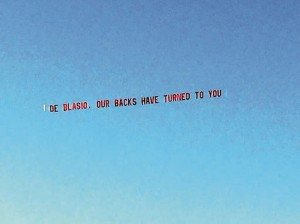 """An airplane on Friday hauling a banner: """"De Blasio, our backs have turned to you."""""""
