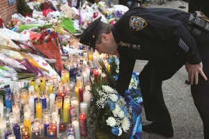 PBA chief Pat Lynch on Monday pays his respects at the makeshift memorial to the two officers.