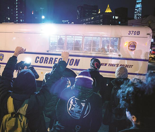 Fellow protesters on Thursday cheer those in police custody in a correction bus at the Manhattan Bridge. (AP Photo/Craig Ruttle)