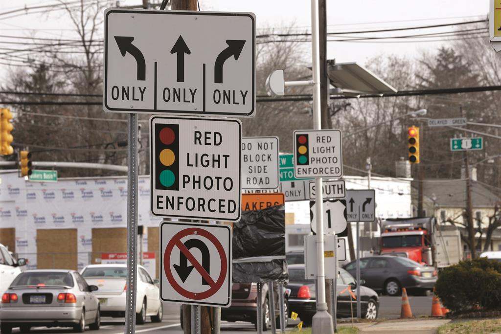 Traffic on Tuesday passes a red-light photo enforcement sign in Lawrence Township, N.J. (AP Photo/Mel Evans)