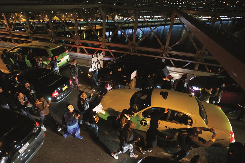 Protesters on Saturday night march over the Brooklyn Bridge, blocking traffic and inconveniencing tens of thousands of drivers. (AP Photo/John Minchillo)