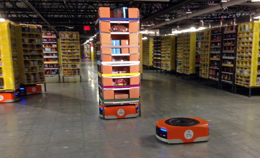 A Kiva robot drive unit is seen in the foreground before it moves under a stack of merchandise pods, at one of Amazon's newest distribution centers, in Tracy, Calif., on Sunday, Nov. 30, 2014. This Amazon Fulfillment Center opened in 2013 and was refitted to use new robot technology in the summer of 2014. All year, Amazon has been investing in ways to make shipping faster and easier to prepare for this year-end shopping season. At this Northern California warehouse, the company is employing robotics and other new technology to help workers process the annual onslaught of shopping orders. (AP Photo/Brandon Bailey)