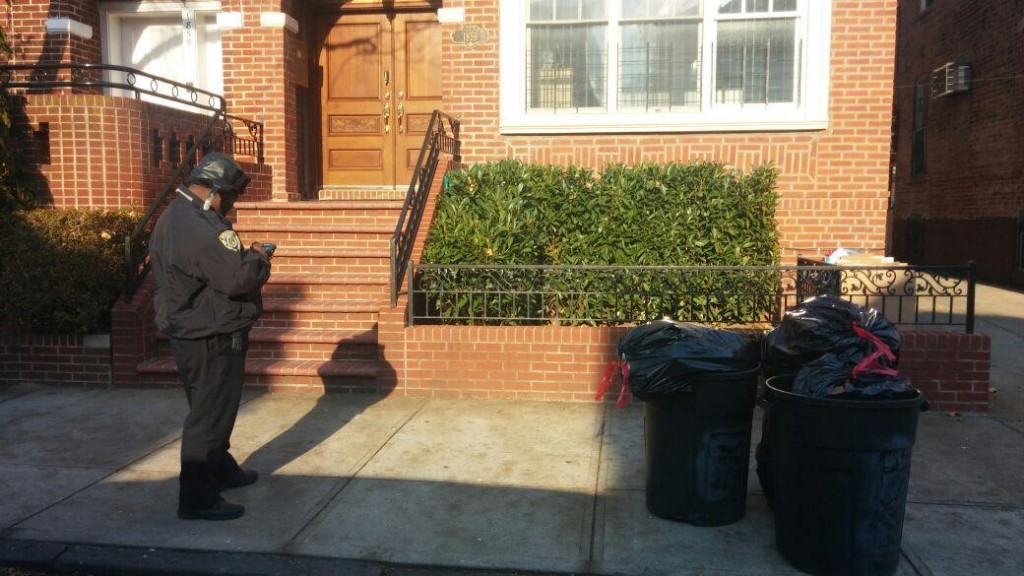 A New York City Sanitation enforcement agent writing a ticket on Friday in Boro Park for a resident who took out the trash too early. (Hamodia Photo)