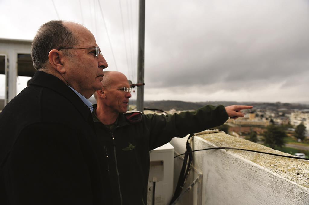 Israeli Defense Minister Moshe Yaalon seen being briefed at an IDF command post. (Hamad Almakt/Flash90)