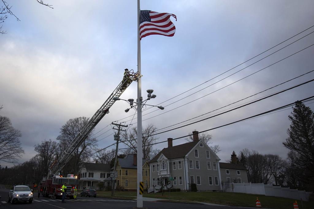 Firefighters lower the American flag to half-staff along Main Street in Newtown, Connecticut, December 14. For a second straight year, the leafy suburb held no public events to commemorate the massacre that left 20 first-graders and six educators dead at Sandy Hook Elementary School, an incident that inflamed the U.S. debate over gun control and mental-health care. (REUTERS/Michelle McLoughlin)