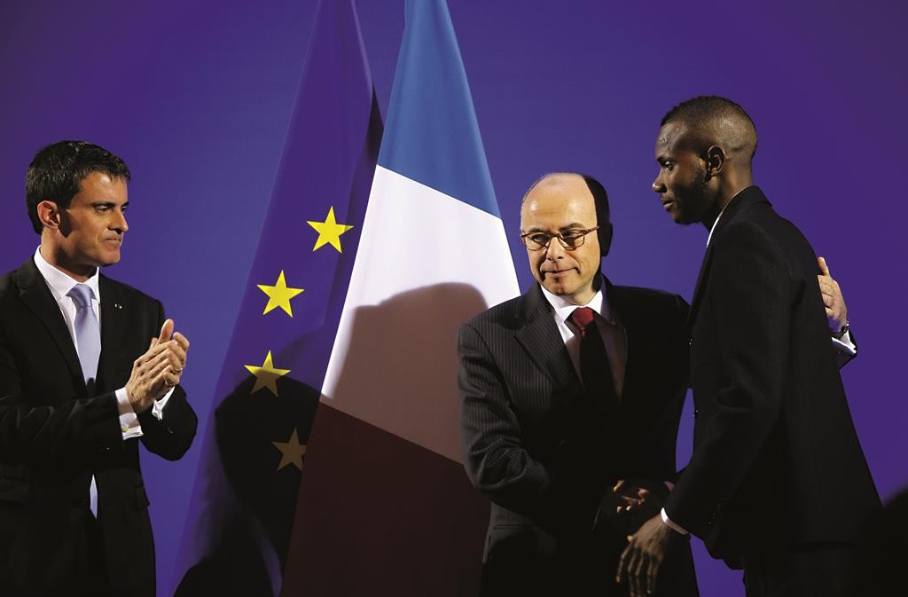 French Prime Minister Manuel Valls (L) and French Interior Minister Bernard Cazeneuve (C) award citizenship to Lassana Bathily during a ceremony in Paris, Tuesday. (AP Photo/Christophe Ena)