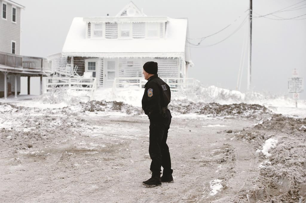 A police officer surveys the scene in Scituate, Mass., Wednesday, the day after a winter storm deposited sand and rocks on the road and coated houses in frozen sea spray.  (AP Photo/Michael Dwyer)