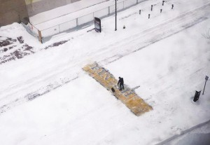 Chris Laudani  shovels snow from the Boston Marathon finish line on Boylston Street, in Boston, during a winter storm that slammed eastern Massachusetts with as much as two feet of snow. (AP Photo/Philip L. Hillman)