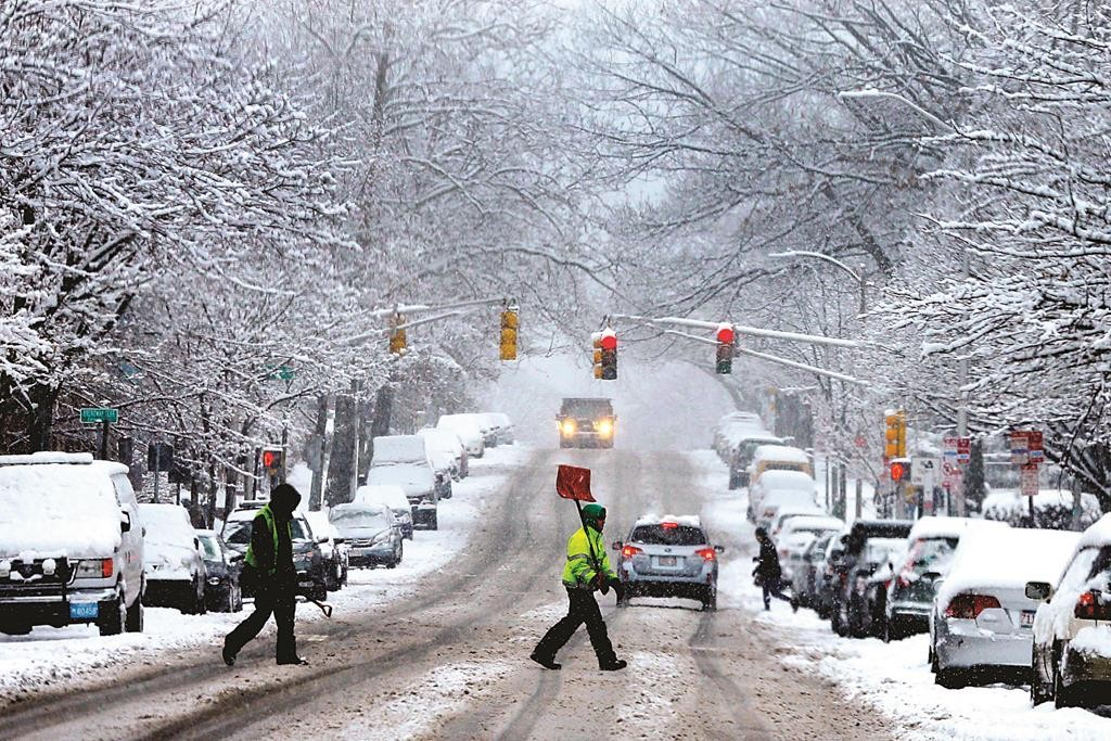 A snow shoveler crosses a street during a winter snowstorm in Cambridge, Massachusetts. (REUTERS/Brian Snyder)
