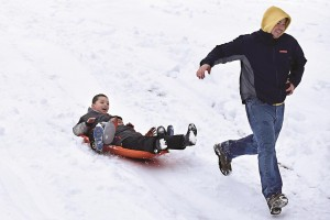 Jose Lora of Paterson runs in front of his sons Steve, 6, and Andy, 4, as they ride a sleigh down a hill at Garret Mountain Reservation in Woodland Park, NJ. (APPhoto/The Record of Bergen County, Michael Karas)