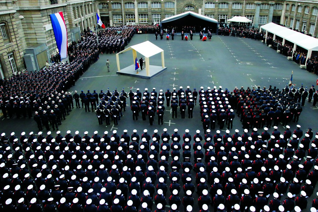 French President Francois Hollande delivers his speech, at left, during a ceremony to pay tribute to the three police officers killed in the attacks, in Paris, France, Tuesday. (AP Photo/Francois Mori, pool)