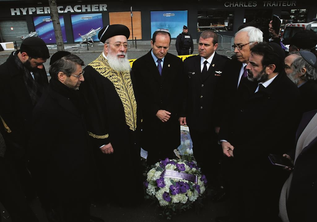 Yerushalayim Mayor Nir Barkat (C) listens as former Israeli Sephardic Chief Rabbi Harav Shlomo Amar (3rd L) speaks after visiting the kosher grocery where Amedy Coulibaly killed four Jews in a terror attack, in Paris, Wednesday. (AP Photo/Christophe Ena)