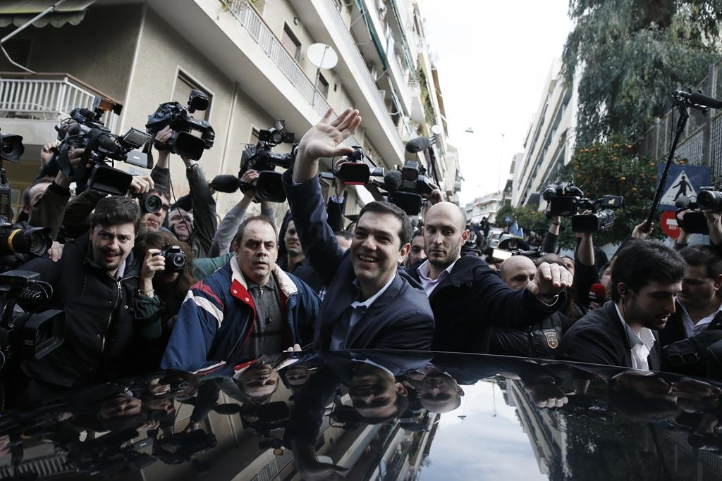 Alexis Tsipras, (C), leader of Greece's Syriza left-wing main opposition, waves to his supporters after voting at a polling station in Athens, on Sunday. (AP Photo/Petros Giannakouris)