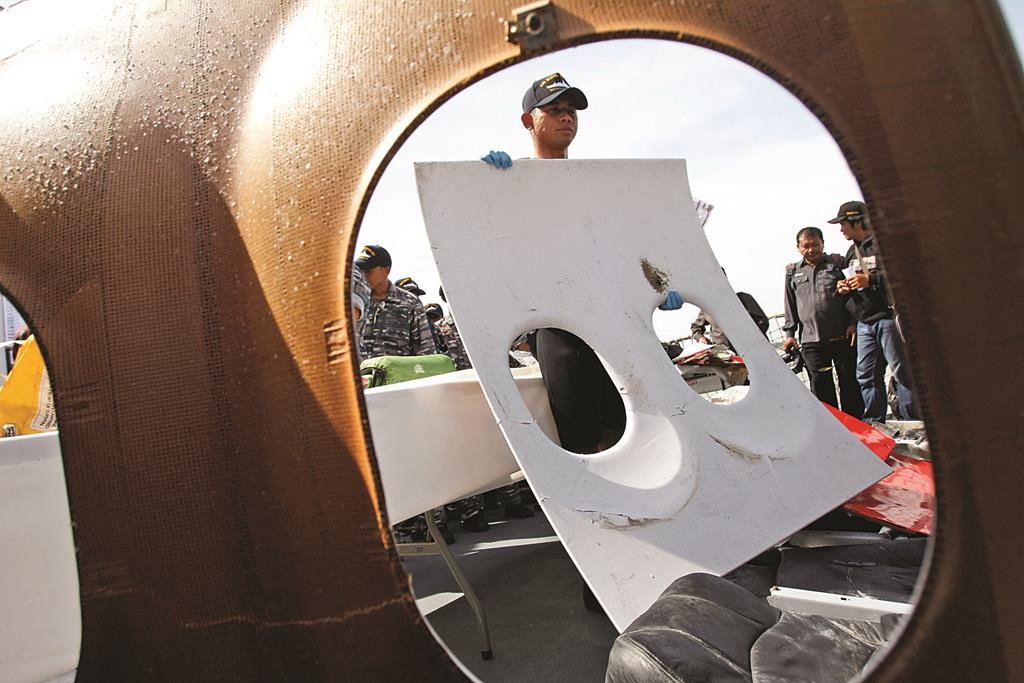 A crew member of Indonesian Navy ship KRI Bung Tomo holds a piece of the window panel of AirAsia Flight 8501 recovered in search operations for the ill-fated jetliner, during a press conference at the Navy's Eastern Fleet Naval Base in Surabaya, East Java, Indonesia, Monday. (AP Photo/Trisnadi)