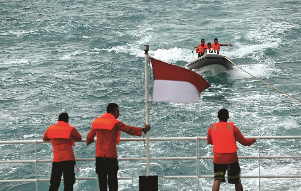 Rescue team members in a boat communicate with other members of the team on the deck of the Search and Rescue ship KN Purworejo during a search operation for passengers onboard AirAsia Flight QZ8501 in the Java Sea on Sunday.