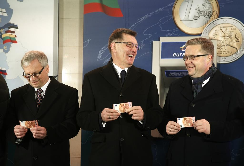 Lithuania's Prime Minister Algirdas Butkevicius (C), Lithuania's Minister of Finance Rimantas Sadzius (L) and Chairman of the Board of the Bank of Lithuania Vitas Vasilaiuskas smile with Euro banknotes which they withdrew from an ATM cash machine in Vilnius, Lithuania, early Thursday. The Baltic state of Lithuania early Thursday became the 19th European Union member to adopt the joint European currency, the euro.  (AP Photo/Mindaugas Kulbis)