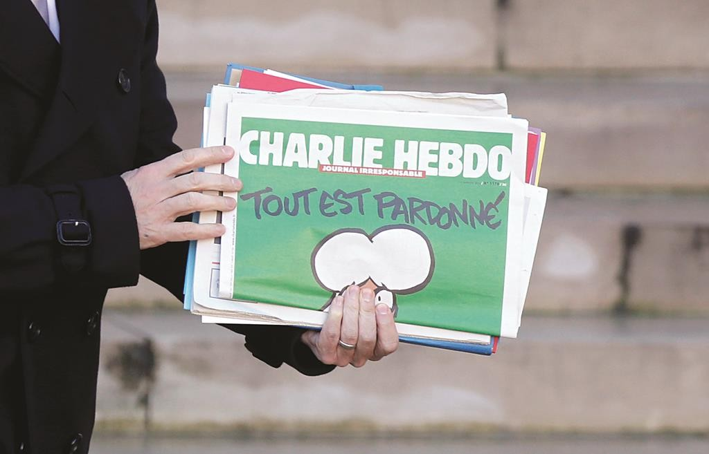 French Prime Minister Manuel Valls holds a copy of Charlie Hebdo as he leaves the weekly cabinet meeting at the Elysee Palace in Paris Wednesday. (REUTERS/Christian Hartmann)