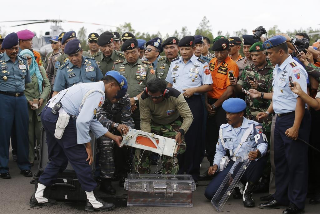 Indonesian Air Force and Indonesian Navy personnel hold one of the black boxes of the ill-fated AirAsia Flight 8501 that crashed in the Java Sea, at airport in Pangkalan Bun, Indonesia, Monday. (AP Photo/Achmad Ibrahim)