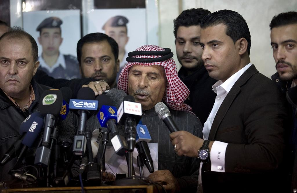 Safi al-Kaseasbeh, (C) father of Jordanian pilot Lt. Muath al-Kaseasbeh, who is held by the Islamic State group terrorists, reads a statement for the media urging his son's captors to have mercy on a fellow Muslim and spare his life, in Amman, Jordan, Thursday. (AP Photo/Nasser Nasser)