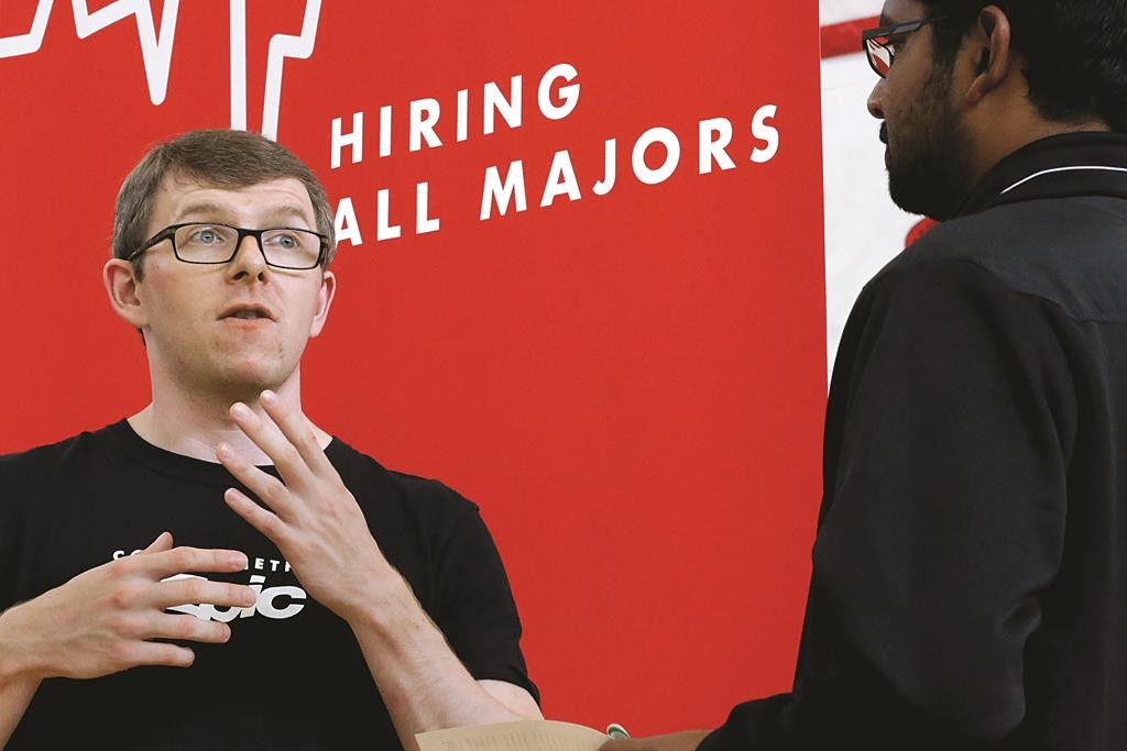 Jacob Robinson (L) of Epic, an electronic health record software company, speaks with students attending The Foot in the Door Career Fair at the University of Illinois Springfield in Springfield, Ill. The Labor Department issues its November report on job openings and labor turnover on Tuesday, Jan. 13, 2015.  (AP Photo/Seth Perlman, File)