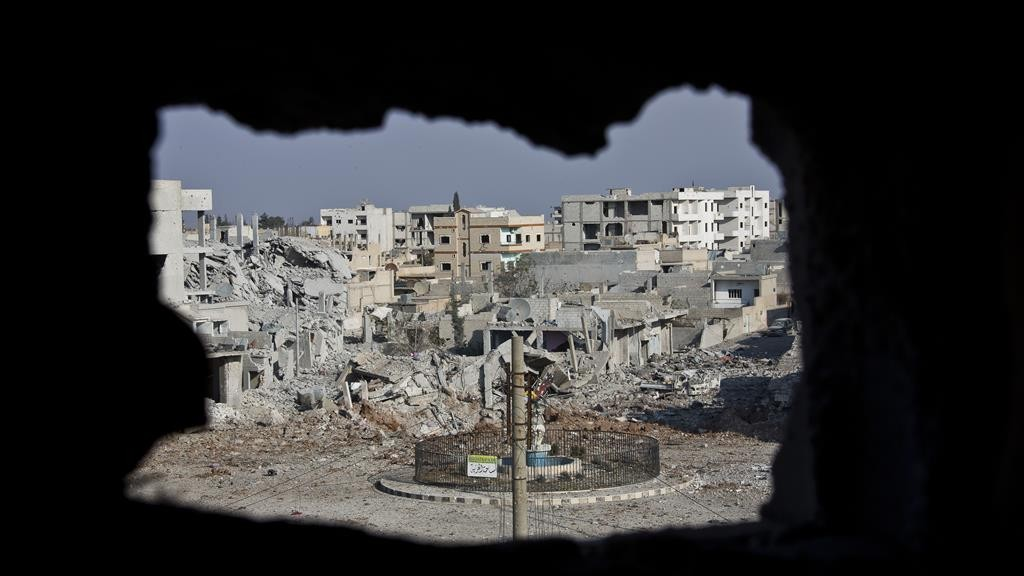 This photo shows an area once controlled by the Islamic State group, past the Qada Azadi roundabout, foreground, in Kobani, Syria.  (AP Photo/Jake Simkin, File)