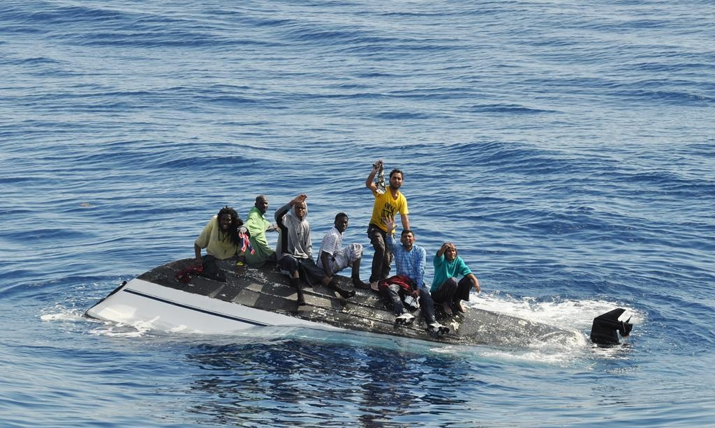 A group of migrants standing on their overturned boat off the coast of Port St. Lucie, Fla. The migrants were from Haiti, India and the Bahamas.  (AP Photo/United States Coast Guard)