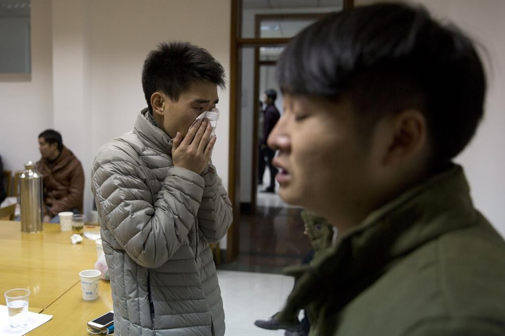 A man who only gave his surname, Zhao, cries after seeing a photo of his relative who was killed in the deadly stampede in Shanghai, China. (AP Photo/Ng Han Guan)