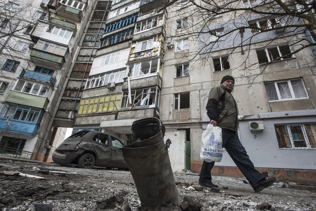 A man walks by a burned car and a piece of exploded Grad missile, outside an apartment building in the Vostochniy district of Mariupol, Eastern Ukraine, on Sunday. (AP Photo/Evgeniy Maloletka)