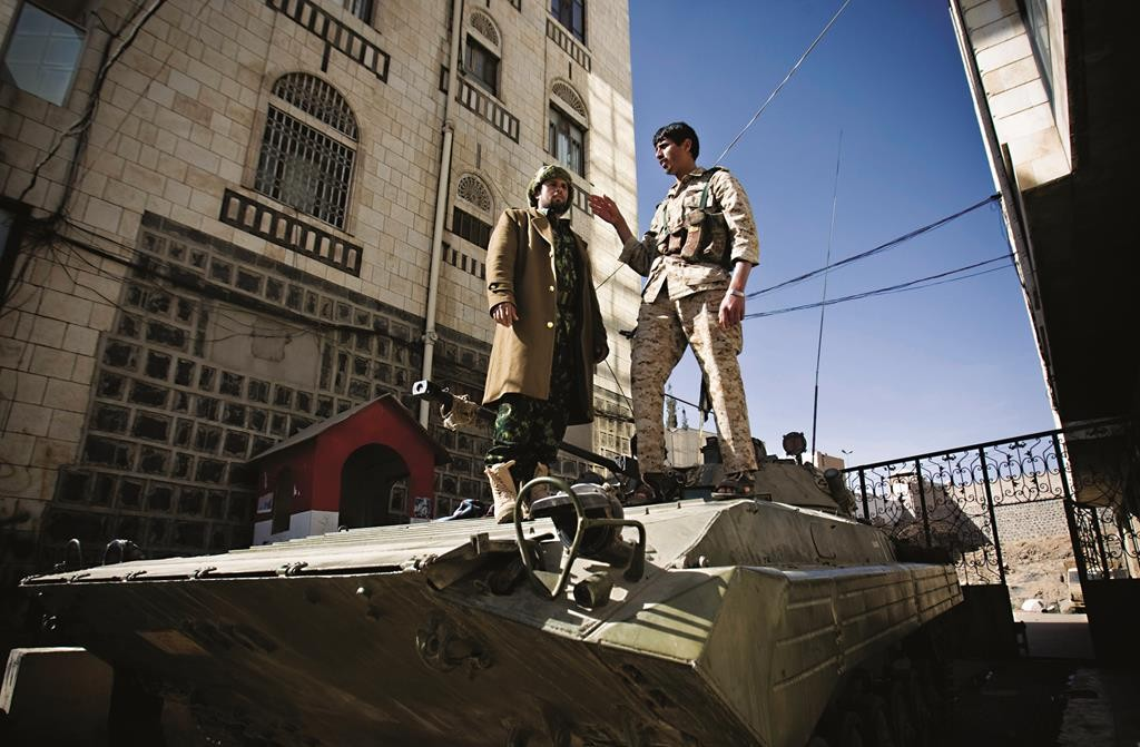 Houthi Shiite Yemeni wearing army uniforms stand atop an armored vehicle — seized from the army during recent clashes — outside the house of Yemen's President Abed Rabbo Mansour Hadi in Sanaa, Yemen, Thursday. (AP Photo/Hani Mohammed)