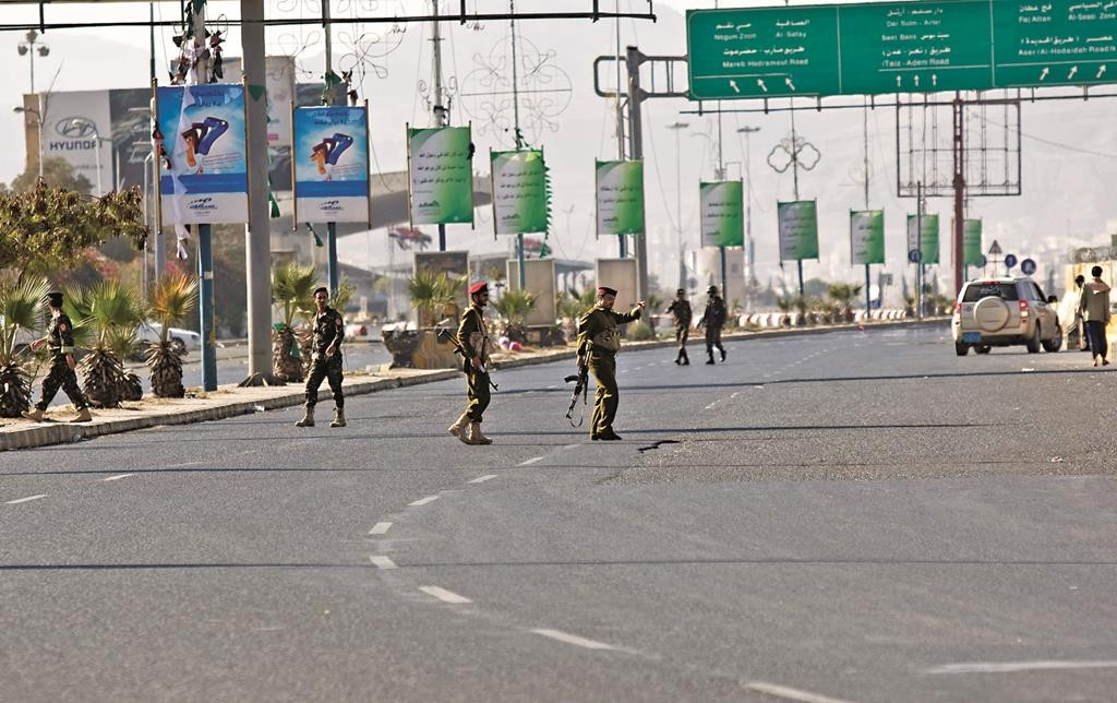 Houthi Shiite Yemenis wearing army uniforms stand guard at a street leading to presidential palace during clashes in Sanaa, Yemen, Monday. (AP Photo/Hani Mohammed)