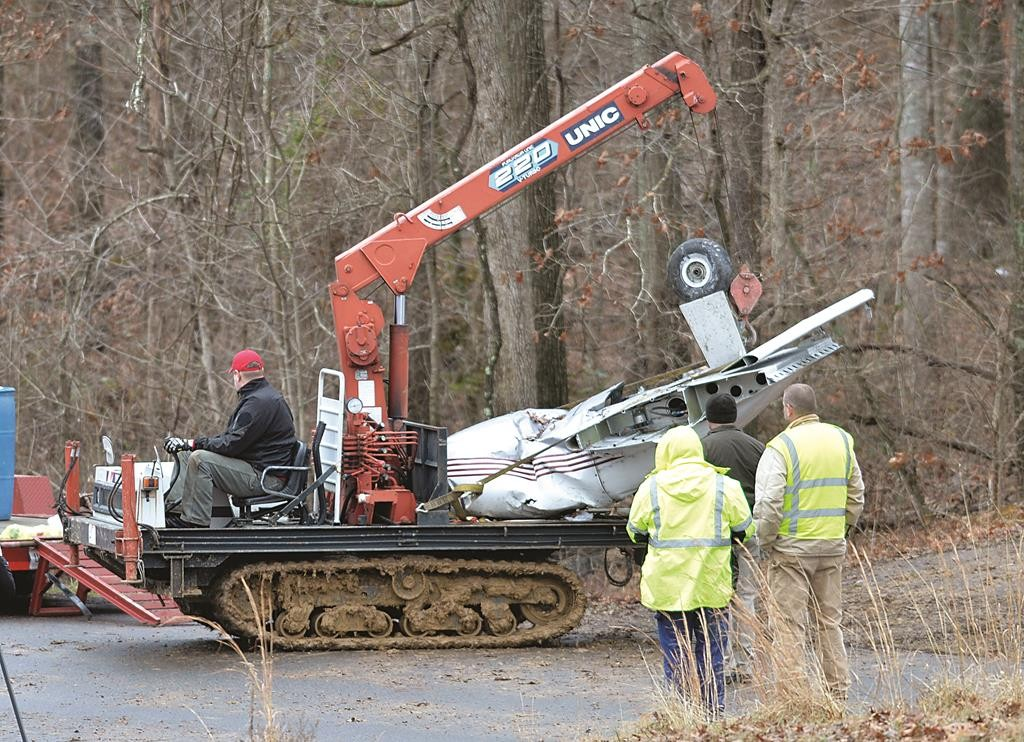 Salvage workers bring out part of a Piper PA-34's fuselage, wing, and landing gear from a crash site Sunday, in Kuttawa, Ky. )AP Photo/Timothy D. Easley)