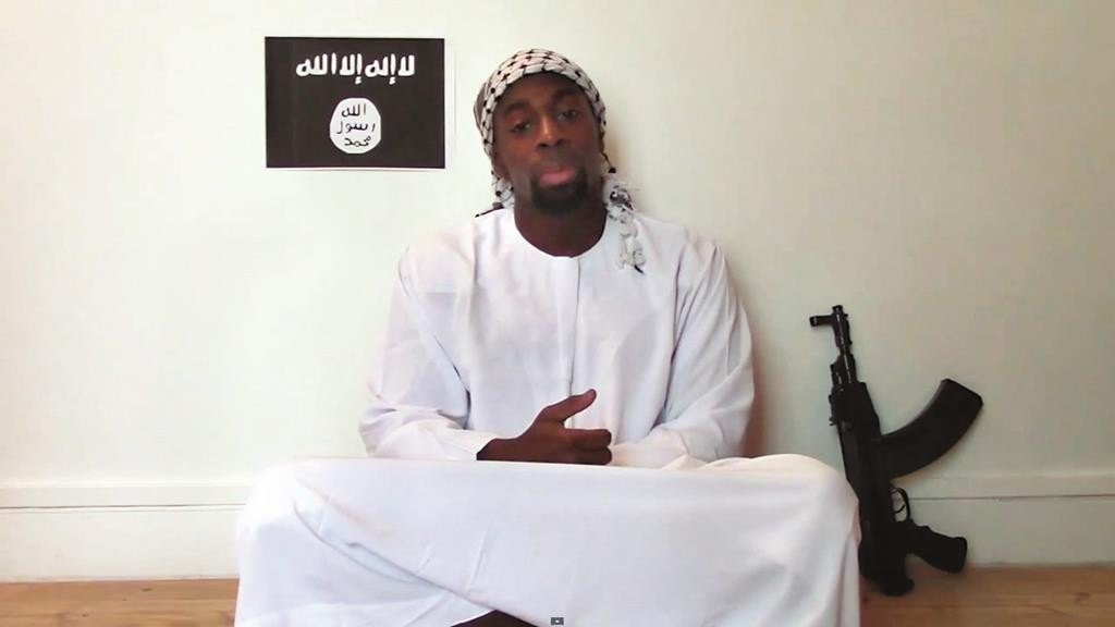 This image made from a video posted online by terrorists on Sunday shows slain hostage-taker Amedy Coulibaly, who shot a policewoman and four hostages at a kosher grocery in Paris, with a gun in front of an Islamic State emblem as he defends the Paris attacks carried out on the satirical newspaper, police and a Jewish store. (AP Photo)