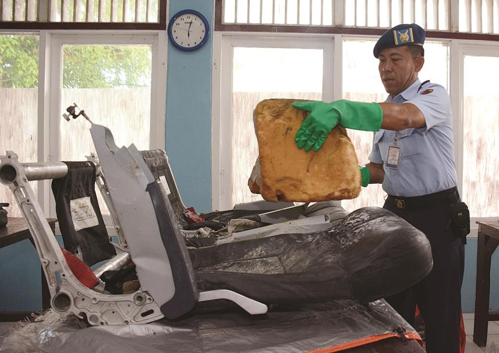 An Air Force officer arranges the remains of airline seats from the ill-fated AirAsia Flight 8501 for investigation purpose, at the military air base in Pangkalan Bun, Central Borneo, Indonesia, Tuesday. (AP Photo/Dewi Nurcahyani)