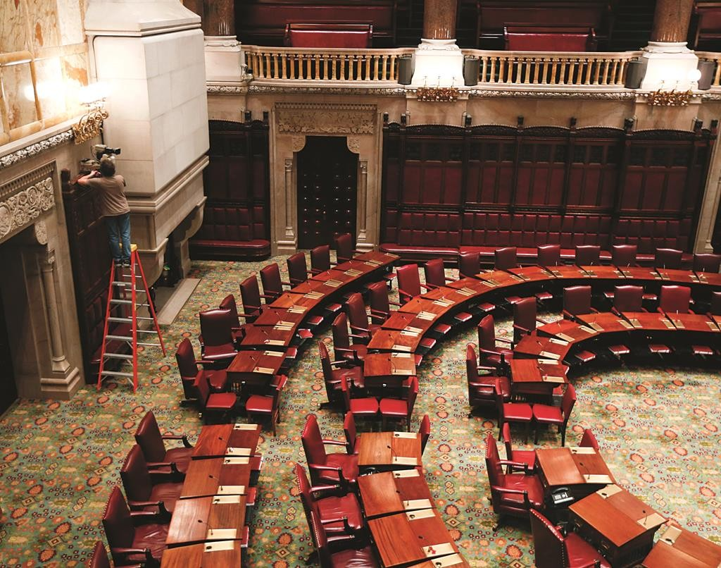 A worker on Tuesday performs maintenance work in the Senate Chamber at the state Capitol in Albany, a day before the 2015 legislative session begins. (AP Photo/Mike Groll)
