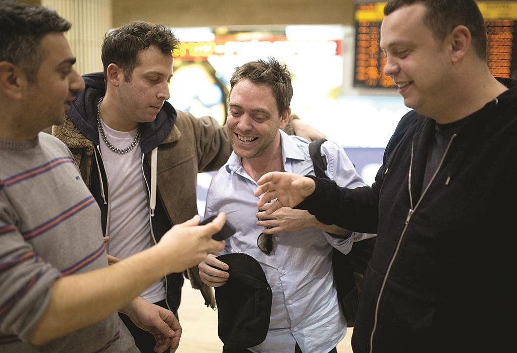 Damian Pachter (2nd R), a journalist with the Buenos Aires Herald, is greeted in the arrivals hall at Ben Gurion International Airport on Sunday. (REUTERS/Amir Cohen)