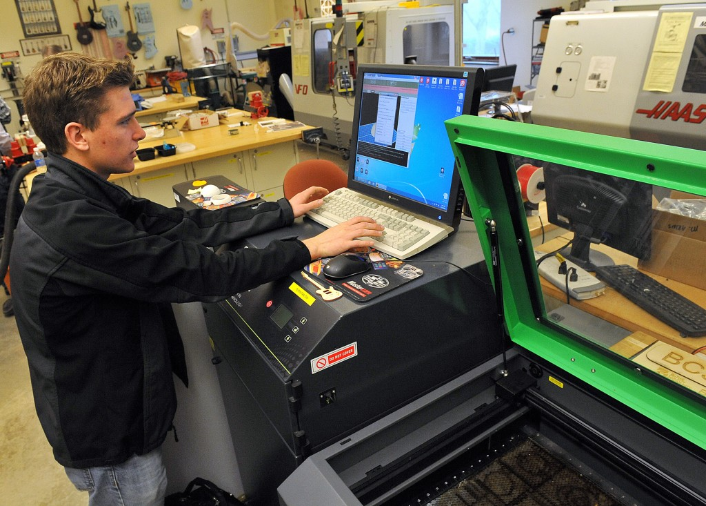 Butler County Community College sophomore Zach Staebler works with the Thingiverse Universal Laser System used to form objects from a computer plan at the school's manufacturing lab. (Bob Donaldson/Pittsburgh Post-Gazette/TNS)
