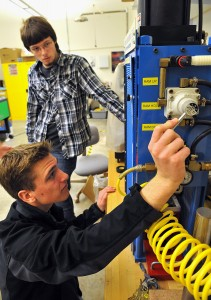 Butler County Community College sophomores Zach Staebler, front, and Mike Paul work an injection-molding machine in the school's manufacturing lab. (Bob Donaldson/Pittsburgh Post-Gazette/TNS)