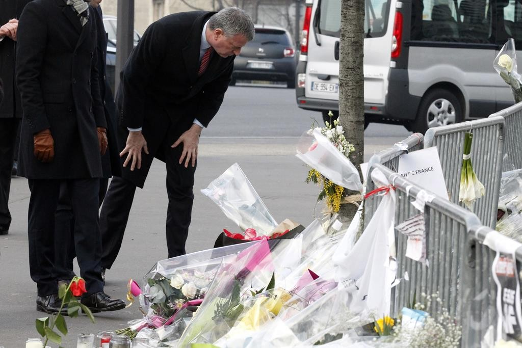 NYC Mayor Bill de Blasio on Tuesday looks at wreaths at the kosher grocery where four Jews were killed in a terror attack in Paris. (AP Photo/Francois Mori)
