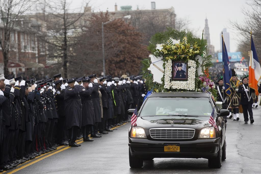 The hearse carrying Officer Wenjian Liu's casket on Sunday passes along 65th Street as police officers salute. (AP Photo)