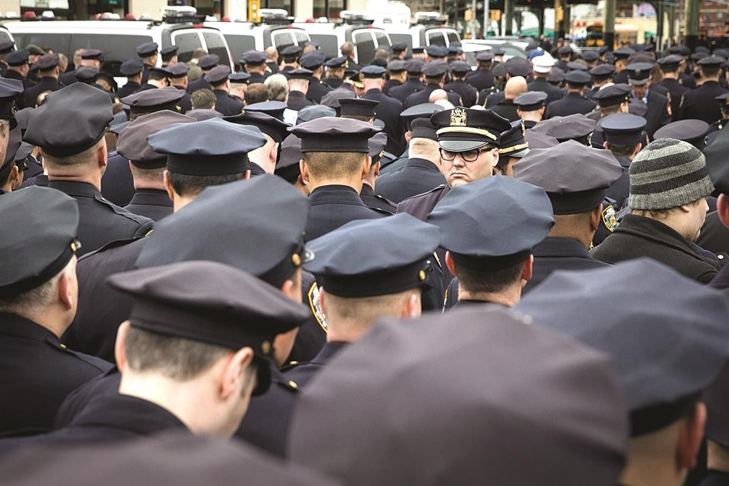 A lone police officer stands facing front as colleagues turn their backs while Mayor Bill de Blasio speaks at the funeral of Officer Wenjian Liu. (All photo credits: News Breakers-AP/John Minchillo-Seth Wenig-Julio Cortez)
