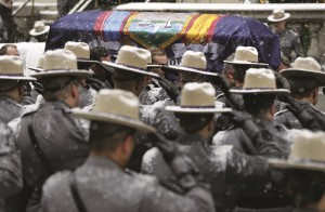 A casket carrying the body of former Gov. Mario Cuomo, draped with the New York state flag, is flanked by state troopers during Cuomo's funeral Tuesday in New York. (AP Photo/Seth Wenig)