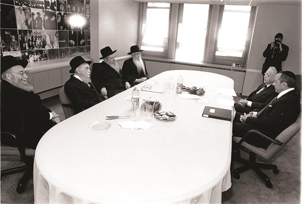 "Gov. Mario Cuomo (R) meeting the Moetzes Gedolei HaTorah in 1994. L-R: Harav Elya Svei, zt""l, Harav Avraham Pam, zt""l, yblc""t, Harav Yaakov Perlow and Harav Aharon Schechter. Rabbi Moshe Sherer, z""l, is seated next to Cuomo. (Agudath Israel/Sender Schwartz)"