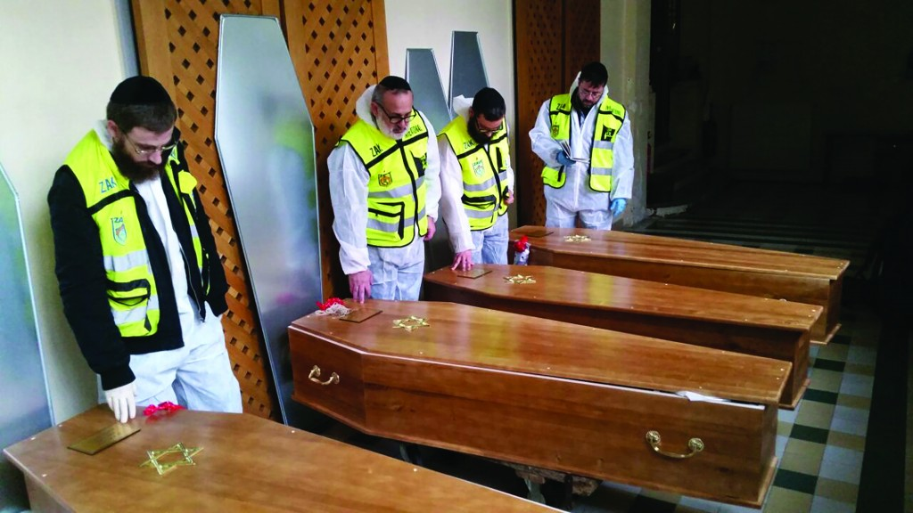 Coffins of the France terror victims being prepared for burial.  (AP Photo/Mati Goldstein, ZAKA)