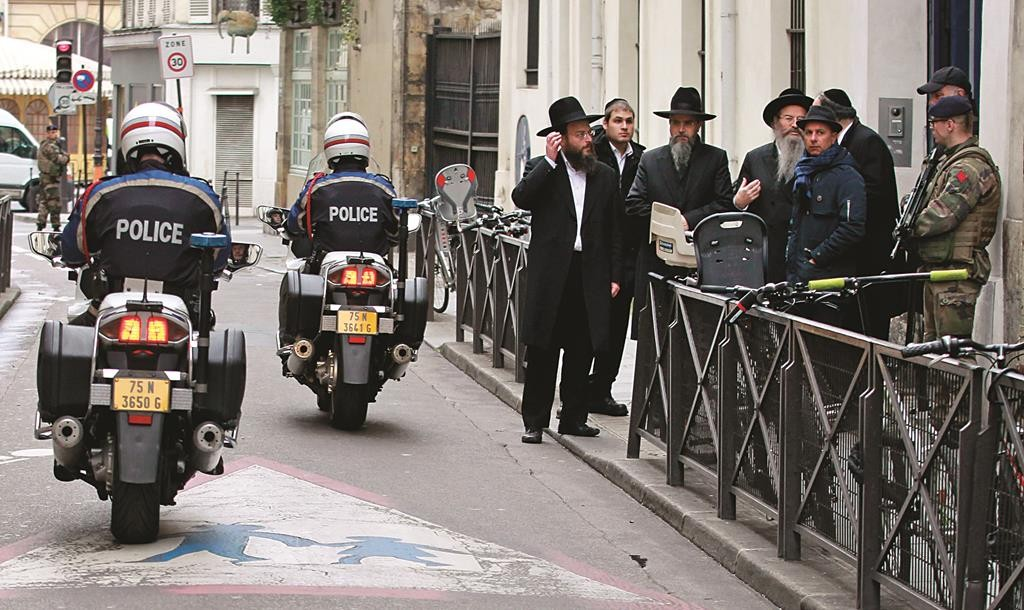 Police officers patrol in front of the Rue Pavée synagogue in the heart of the Jewish quarter in Paris, Monday. (AP Photo/Remy de la Mauviniere)