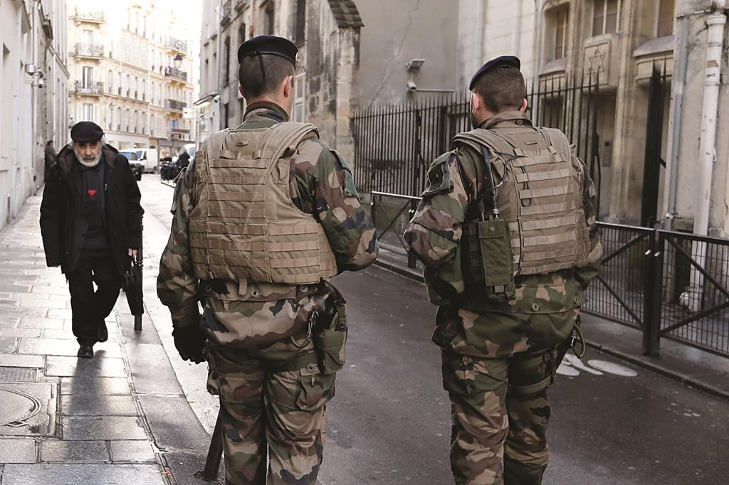 French soldiers patrol a street near a school and a shul in a Jewish neighborhood in Paris on Wednesday as the country remains on high alert after last week's Islamic attacks in the city. (REUTERS/Gonzalo Fuentes)