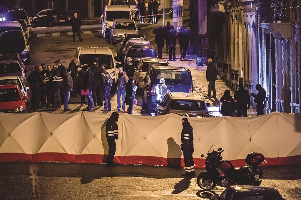 Belgian police officers gather behind a screen as they investigate a a shootout in an anti-terrorist raid in a street in Verviers, Belgium, Thursday. (AP Photo/Geert Vanden Wijngaert)
