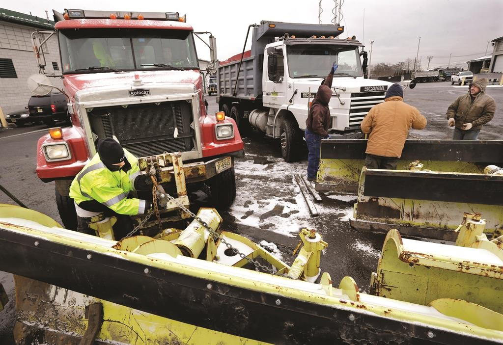 Workers attach snow plows to trucks at a New Jersey Department of Transportation maintenance yard, Monday. (AP Photo/Mel Evans)