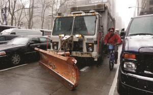 A cyclist navigates between a New York DSNY truck with a snow plow attached, and parked cars on New York's Sixth Ave., Monday. (AP Photo/Richard Drew)
