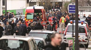 Police officers and rescue workers gather at the scene after gunmen stormed a French newspaper, in Paris, Wednesday. (AP Photo/Remy de la Mauviniere)